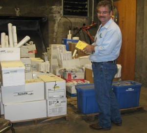 Lyle standing next to a couple of pallets of printed final documentation for a construction project.
