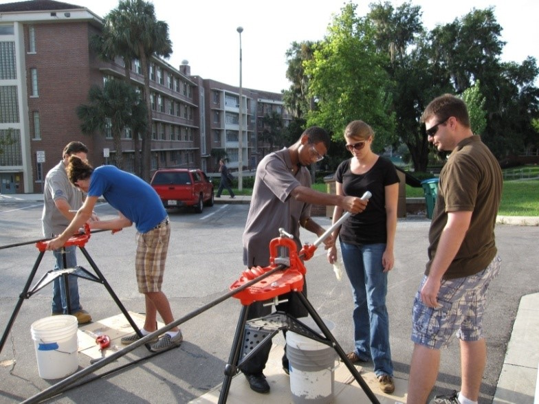 Student volunteers teach their peers how to thread pipe on the drive infront of the Perry Yard